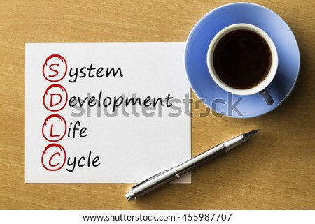 SDLC - System Development Life Cycle - handwriting on notebook with cup of coffee and pen, acronym business concept - stock photo