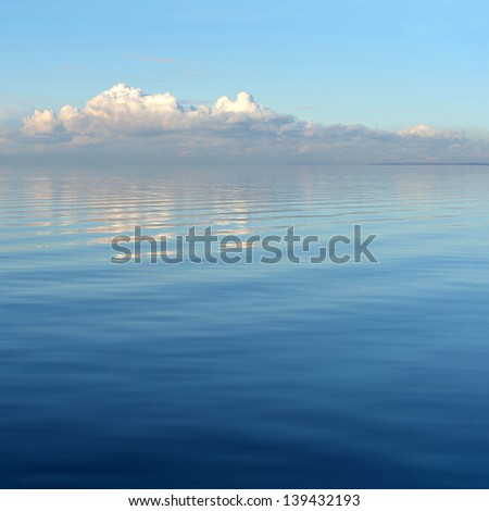 Sea and clouds reflected - stock photo