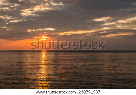 Sea and cloudy sky in sunset time - stock photo