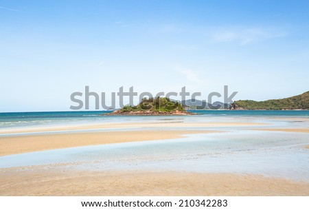 Sea beach and small island in ebb tide time under blue sky - stock photo