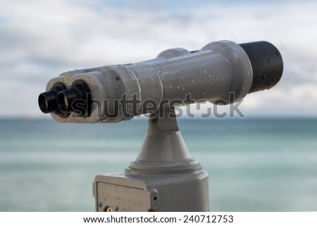 sea binoculars working with coins by the Black Sea shore. some ships on the horizon.  - stock photo