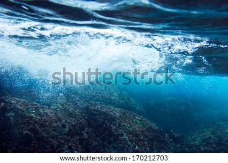 Sea bottom with blue water wave splash background - stock photo