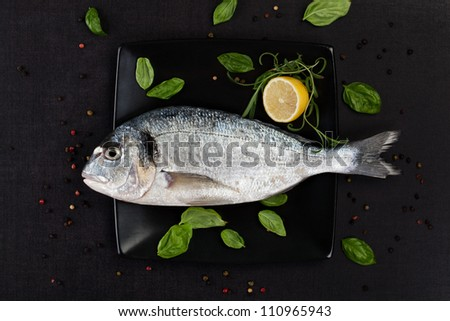 Sea bream on black square plate with colorful peppercorns, fresh basil and rosemary leaves and lemon, top view. Culinary luxurious seafood concept. - stock photo