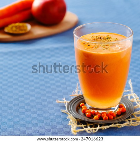 Sea buckthorn, apple and carrot smoothie with pollen - stock photo