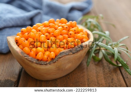 Sea-buckthorn berries in bowl on a wooden background - stock photo
