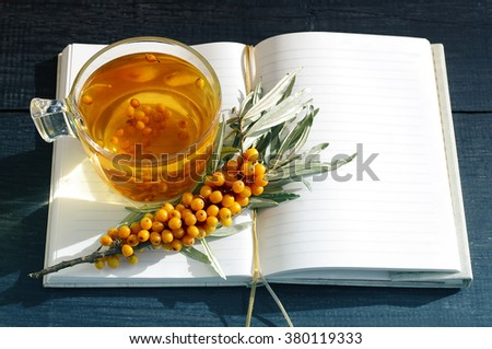Sea buckthorn tea and branch of a sea buckthorn and open pure notebook. Useful drink for health. Herbal tea. Traditional medicine. - stock photo