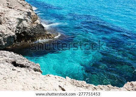 Sea Caves. Transparent sea water. Rocky coast. Beautiful lagoon on Cyprus. Diving spot. - stock photo