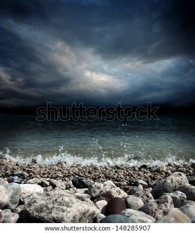 sea coast, stones, waves and dark dramatic stormy sky landscape - shallow DOF - stock photo