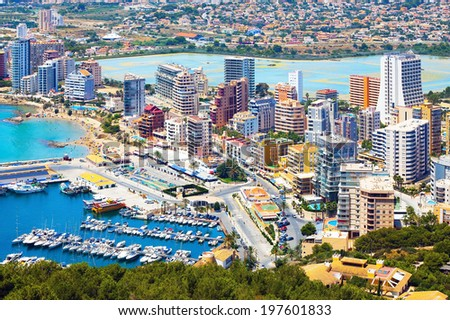 Sea coast with a beach and yacht in a bay on the background of the city (Spain, Costa Brava) - stock photo