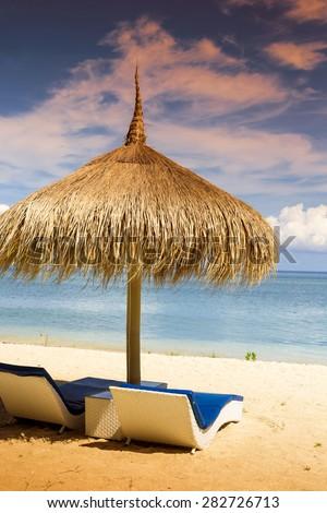 Sea Coastline with Grass Sun Umbrella and Beach Beds. - stock photo