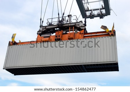 Sea container lifted by a harbor crane  - stock photo