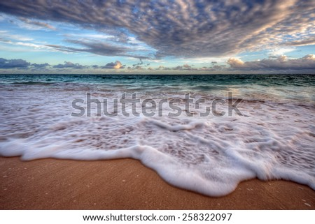 Sea foam breaking onto a sandy beach from azure waters under stormy clouds - stock photo