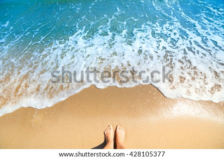 Sea foam, waves and naked feet on a sand beach. Holidays, relax, summer background - stock photo