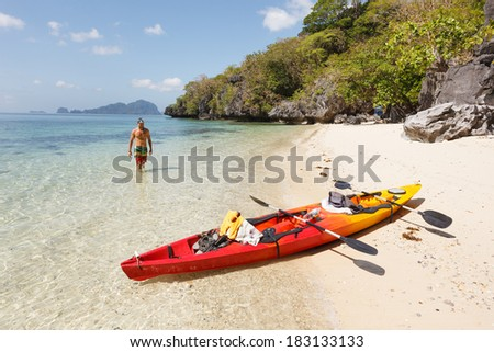 Sea kayak at the lonely sandy beach - stock photo