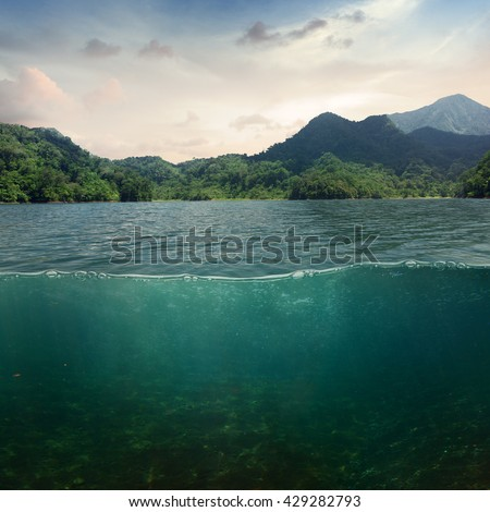 Sea landscape design template with underwater part and coast mountain splitted by waterline - stock photo