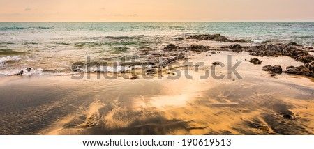 Sea landscape with waves on the beach against sunset - stock photo