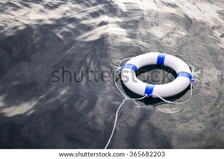Sea life saver float on the sea surface - stock photo