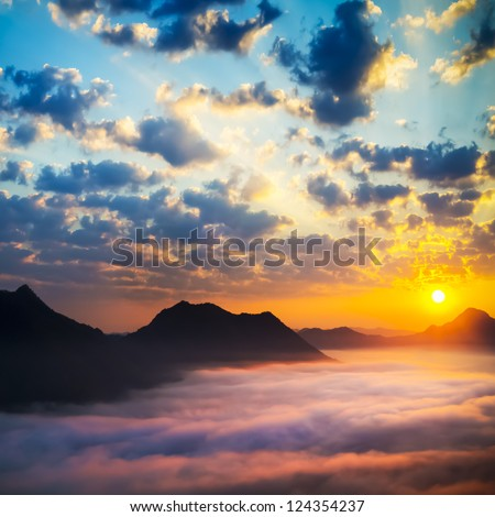 Sea of clouds on sunrise with ray lighting - stock photo
