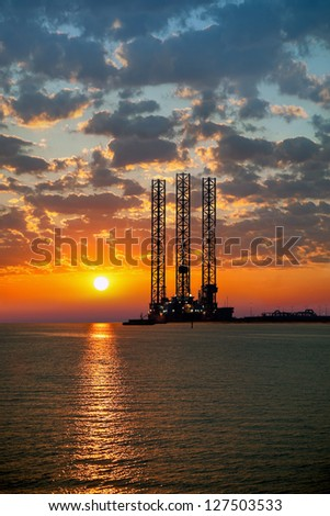 Sea oil rig on sunrise. - stock photo