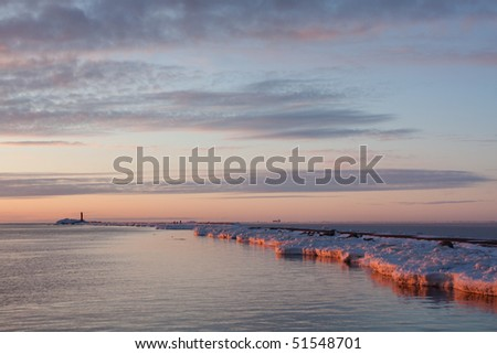 Sea on sunset with lighthouse in winter - stock photo