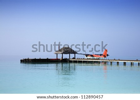 Sea plane docked at the arrival pier of a holiday resort in the Maldives - stock photo