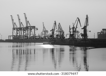 Sea port with cranes and docks early in the morning - stock photo