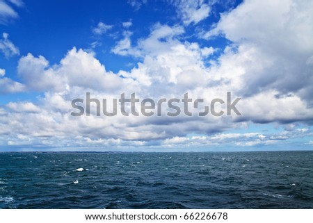 Sea ripples under cloudy sky; sea shore on horizon - stock photo