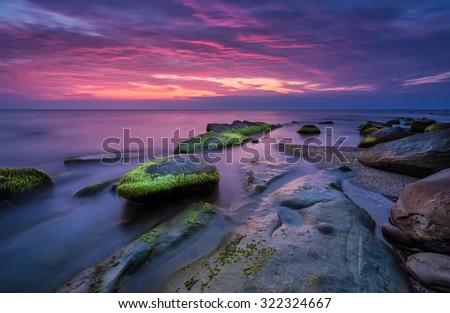 Sea rocks at sunrise. Magnificent sunrise view in the blue hour at the Black sea coast, Bulgaria - stock photo