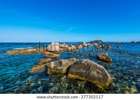 Sea rocks near Nora, Sardinia. View of ancient tower lighthouse, Pula, Sardegna, Italy. Boulder ridge on seashore and Sardegna San Elfisio tower. Sardegna landscape - stock photo
