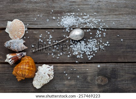 sea salt crystals and a silver spoon on a rustic wooden table - stock photo