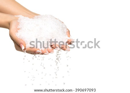 Sea salt crystals in women hand on white background - stock photo