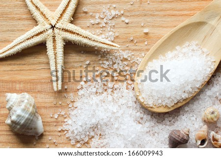 Sea salt crystals in wooden spoon with sea shells and starfish on wooden background - stock photo