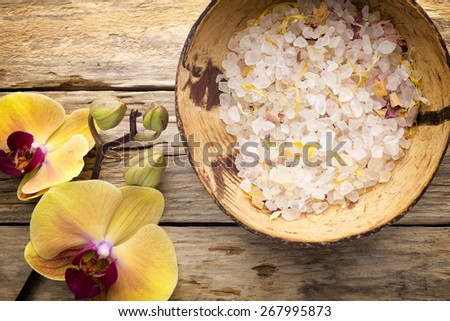 Sea salt in a bowl on a wooden table, yellow orchid. - stock photo