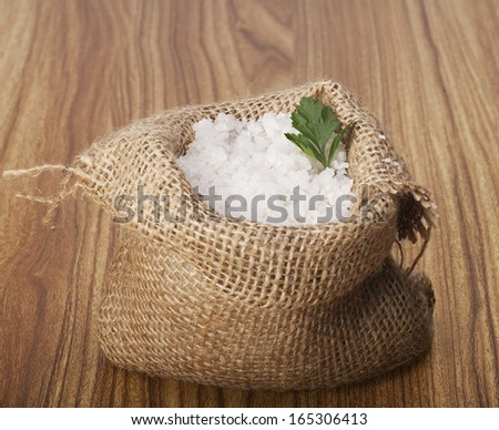 Sea salt in a jute sack on a wooden background. - stock photo