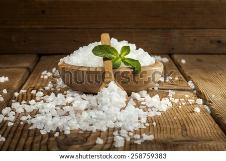 Sea salt in bowl and spoon on a wooden background. - stock photo