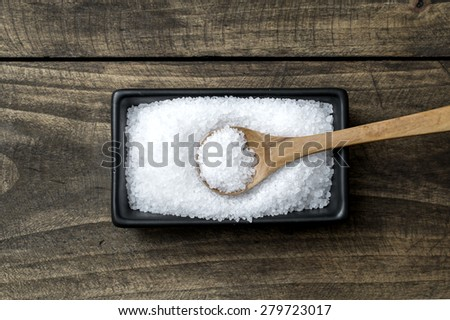 sea salt in  bowl and spoon on wooden table - stock photo
