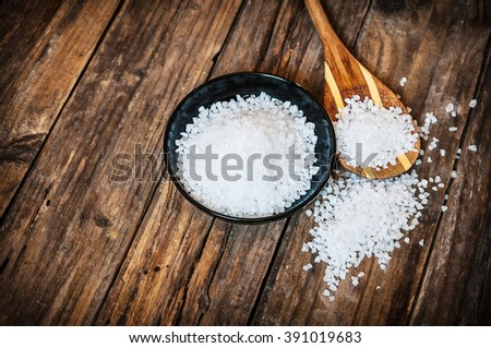 Sea salt in bowl on wooden background - stock photo