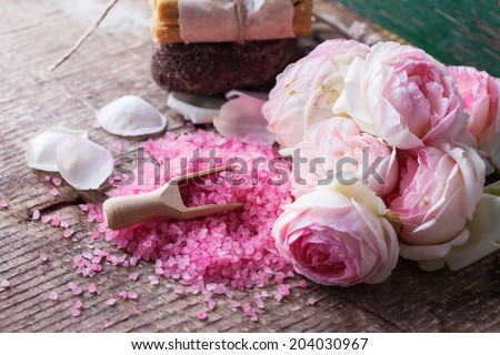 Sea salt in bowl with roses on wooden background. Spa setting. Selective focus, horizontal. - stock photo