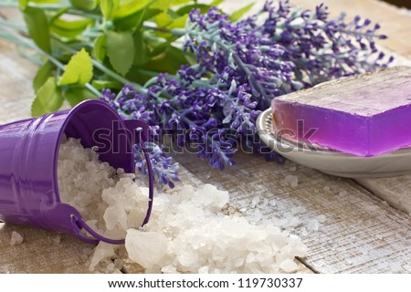Sea salt in bucket with soap and lavender on wooden background. Selective focus. - stock photo