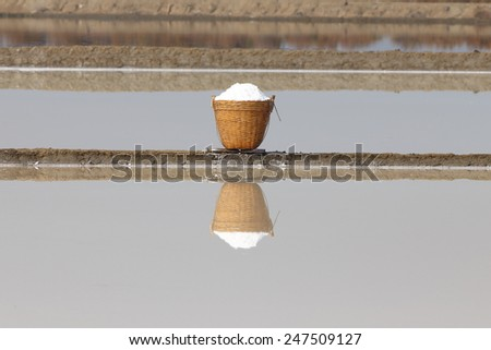 Sea salt in the bamboo basket and its reflection on salt farm. - stock photo
