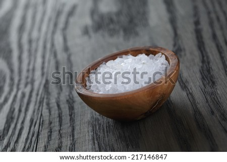 sea salt in wooden bowl for cooking or spa, on dark oak table - stock photo