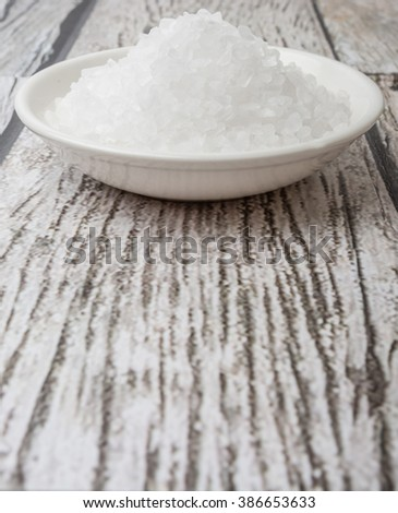 Sea salt in wooden bowl over wooden background - stock photo