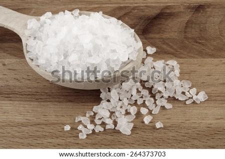 Sea salt in wooden spoon on wooden background - stock photo