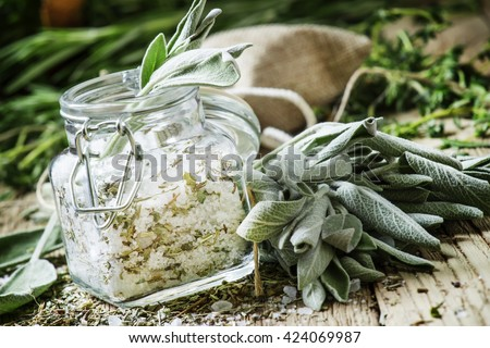 Sea salt, milled with sage in a glass jar, fresh herbs, vintage wooden background, selective focus - stock photo
