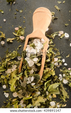 sea salt mix with dried and shredded basil and wooden spoon - stock photo