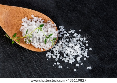 Sea salt on a wooden spoon over black slate background, selective focus, close up - stock photo