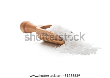 Sea salt poured from wooden scoop - stock photo