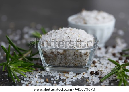 Sea salt scented herb rosemary on black stone background, natural light. Selective focus. - stock photo