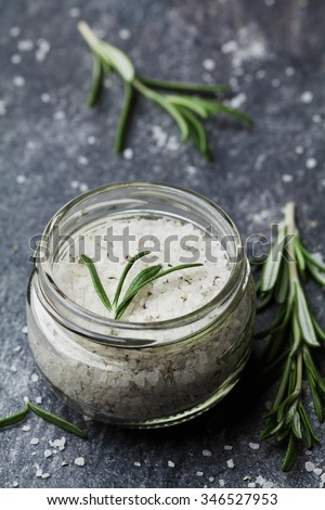 Sea salt scented herb rosemary on black stone background, vintage style - stock photo