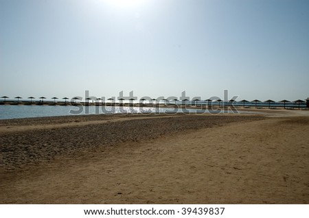 Sea sandy beach with umbrellas and chaise lounges - stock photo